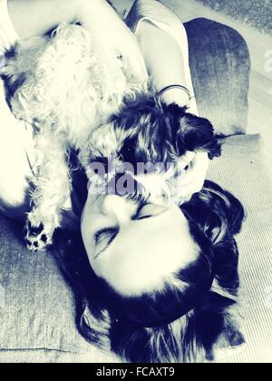 High Angle View Of Young Woman Lying With Maltipoo Poodle On Sofa - Stock Photo
