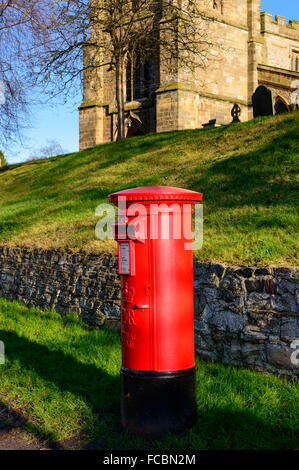 A rural British red traditional Royal Mail pillar box. With St Mary's church - behind. In Wymeswold, on 15th January - Stock Photo
