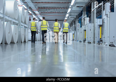 Workers in reflective clothing walking past large paper spools in printing plant - Stock Photo