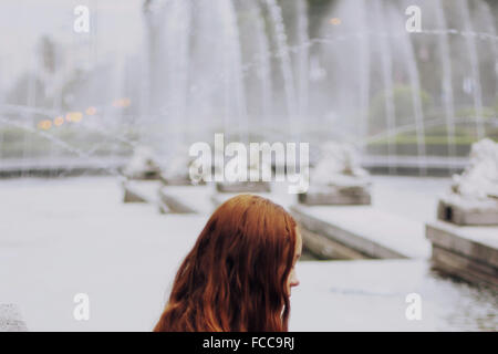 Close-Up Of A Thoughtful Redhead Girl Against Fountain - Stock Photo