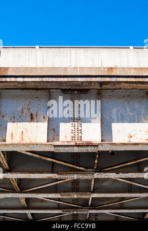 Edge of underside of old rusted steel bridge truss and frame, with rusty rivets and plates, against piece of clear - Stock Photo