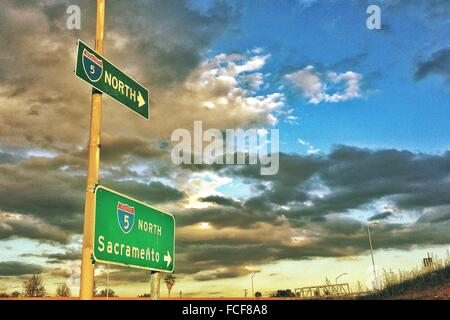 Low Angle View Of Road Sign Against Cloudy Sky - Stock Photo
