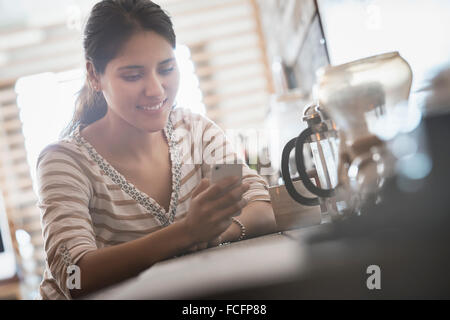 Loft living. A woman looking at her smart phone. - Stock Photo
