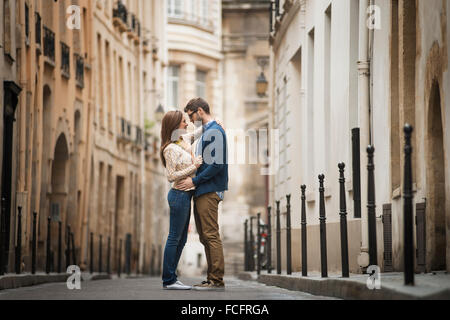 A couple standing gazing at each other, in a narrow street in a city. - Stock Photo