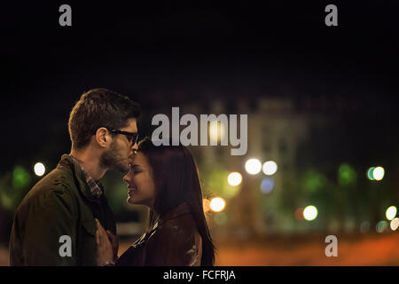 A couple kissing in a city at night. - Stock Photo