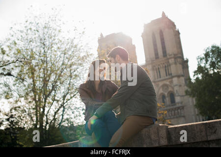 A couple in a romantic mood, side by side with arms around each other outside Notre Dame Cathedral in Paris. - Stock Photo
