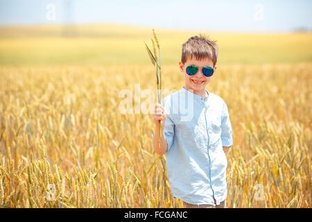 Cute little boy walking happily in wheat field - Stock Photo