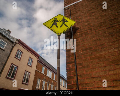 Neon yellow school crossing sign in front of brick wall on a street lined with buildings in Quebec City, Quebec, - Stock Photo