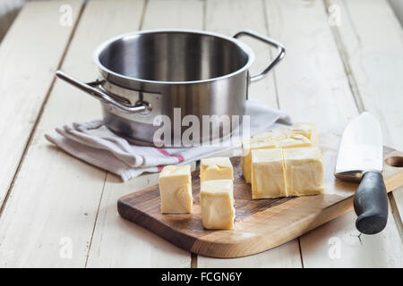 Diced butter on cutting board for preparing ghee - Stock Photo
