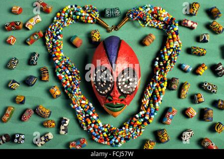 Beaded Kenyan necklace with small Cameroon'passport' mask and West Africcan glass beads. - Stock Photo