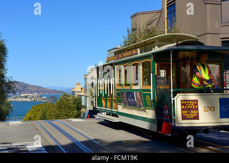 Cable car on Hyde Street at junction with Lombard Street, with distant view of Alcatraz Island, San Francisco, California, - Stock Photo