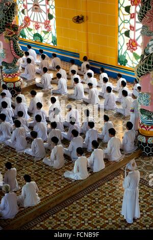 Main priest standing by Caodaist disciples sitting during ceremony, Cao Dai Temple, Tay Ninh (100 km NW of HCMC), - Stock Photo