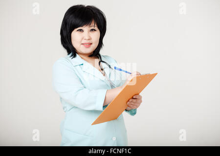 Asian brunette nurse with stethoscope around neck and folder in her hands ready to record patient information, provides - Stock Photo