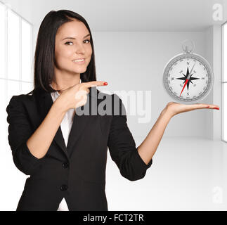 Office girl standing on background of light interior and holding compass - Stock Photo