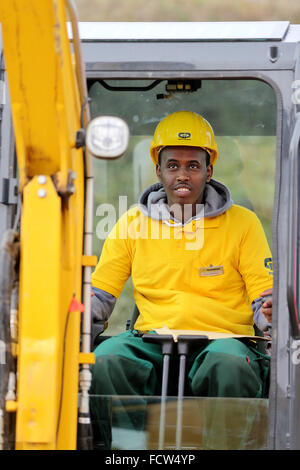Future apprentice Ayanie Osman Hosh from Somalia sits in a small excavator in Halle/Saale, Germany, 25 January 2016. - Stock Photo