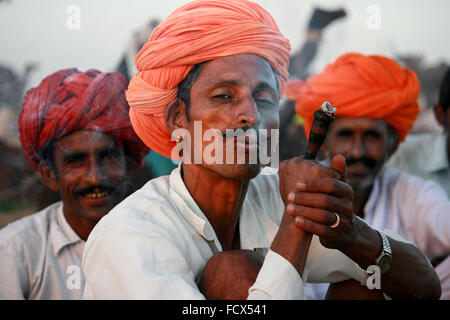 Rajasthani camel drivers smoking chillum, with orange turban , in Pushkar, rajasthan - Stock Photo