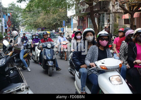 Scooters with riders, some wearing face masks, on a busy street in Hanoi, Vietnam - Stock Photo