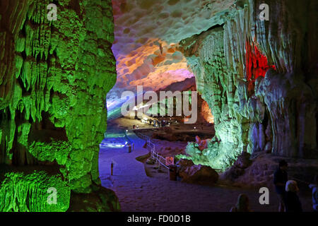 Visitors in a large cave with stalactite and stalagmite formations, Dau Go Cave, in a limestone karst in Halong - Stock Photo