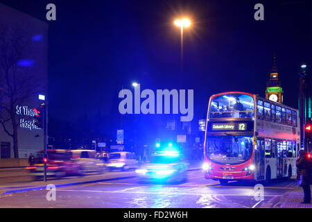 Met police car with blue flashing lights illuminating night sky on Westminster Bridge with London bus waiting at - Stock Photo