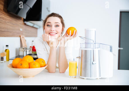 Beautiful happy woman using juicer for making orange juice in the kitchen - Stock Photo