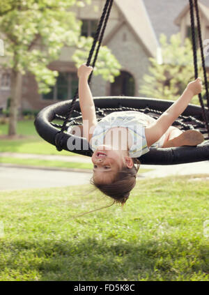Young girl hanging upside down from her swing and smiling. - Stock Photo