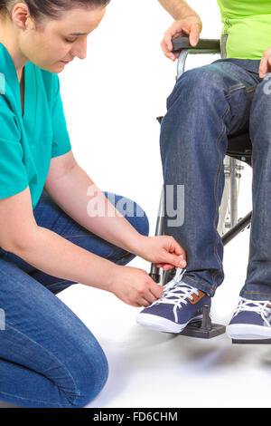Nurse helping a disabled young man in wheelchair get dressed. - Stock Photo