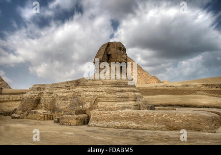 The Sphinx guarding the pyramids on the Giza plateu in Cairo, egypt. - Stock Photo