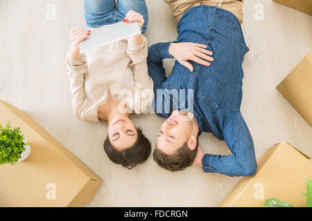 Loving couple lying on the floor - Stock Photo