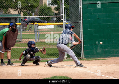 Batter swinging at ball in boys age 12 youth baseball game. St Paul Minnesota MN USA - Stock Photo