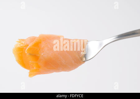 slice of smoked salmon on silver fork - Stock Photo