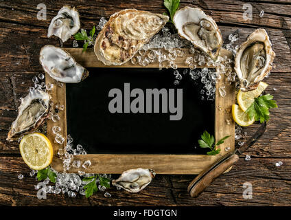 Oysters served on wood with blackboard - Stock Photo