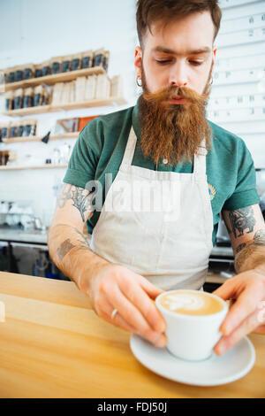 Handsome man preparing coffee in coffee shop - Stock Photo