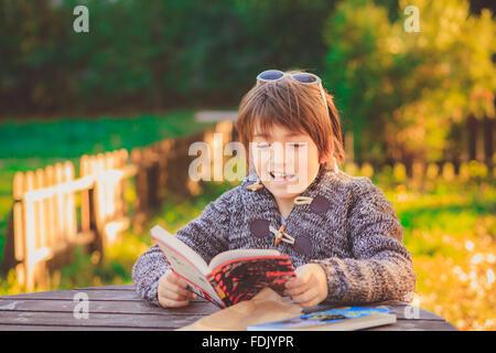 Boy reading book in garden - Stock Photo