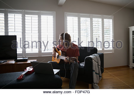 Man with headphones playing guitar in living room - Stock Photo