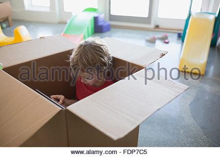 Boy using digital tablet inside cardboard box - Stock Photo