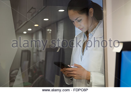 Doctor texting at glass wall in clinic - Stock Photo