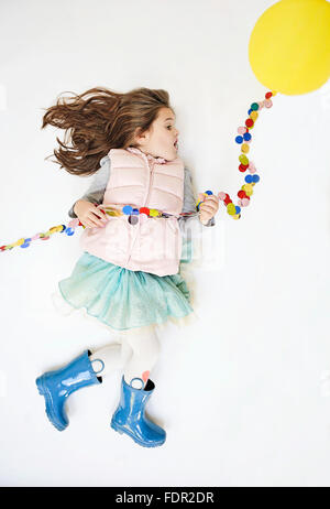 Little girl pretending to take flight by means of a yellow balloon. - Stock Photo