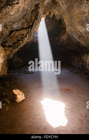 A beam of sunlight shining into a lava tube in Mojave National Preserve, California - Stock Photo