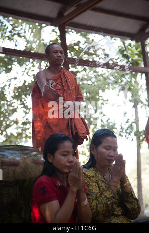 A Buddhist monk is blessing two travelers, a water ceremony,from the temple Bayon, Siem Reap. Cambodia - Stock Photo