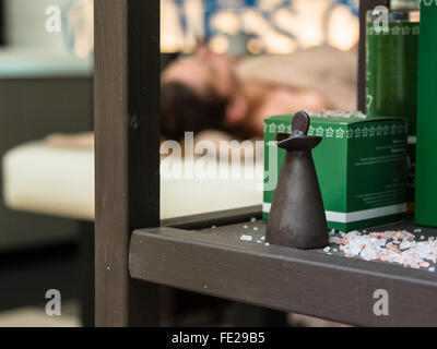 Spa Setting on Wooden Shelf, Masseuse doing Massage in background - Stock Photo