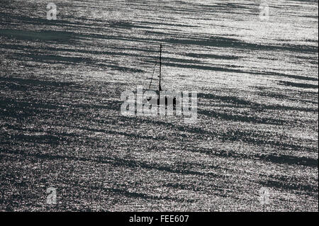 A yacht sails off the coast near Falmouth, in Cornwall, Britain October 28, 2011. Photograph by John Voos - Stock Photo