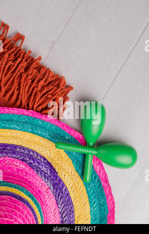 Mexican sombrero, blanket and pair of maracas on wood background. - Stock Photo