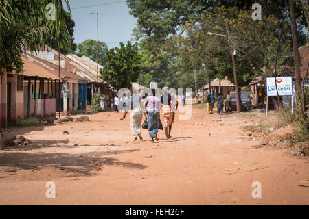 Villagers walk down the unpaved street in a northern Guinea Bissau town - Stock Photo