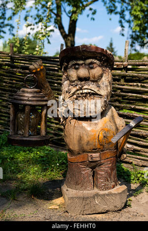 A wooden statue of a miner dwarf in Dubno Castle, Rovno Region, Ukraine - Stock Photo