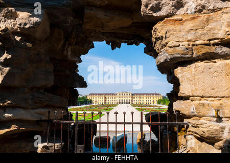 View of the Schonbrunn Palace in Vienna through a fountain cave frame - Stock Photo