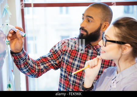 Young business people discussing of something in office - Stock Photo