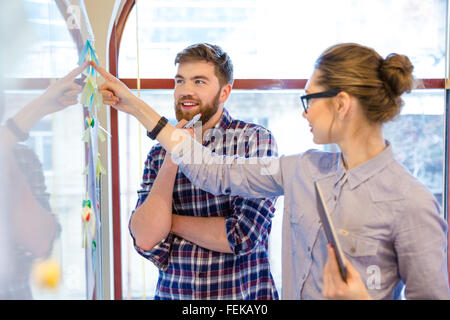 Casual business people working with whiteboard in office - Stock Photo