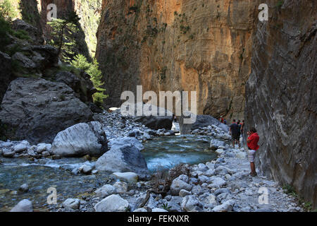 Crete, traveller in the Samaria gulch, way by the brook bed along in high cliff faces - Stock Photo