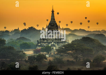 Scenic sunrise with many hot air balloons above Bagan in Myanmar - Stock Photo