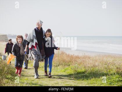 Multi-generation family walking on grassy beach path - Stock Photo
